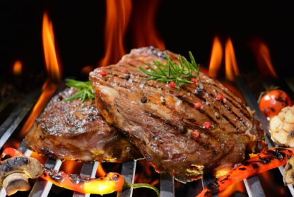 Grilled beef steak with vegetable on the flaming grill