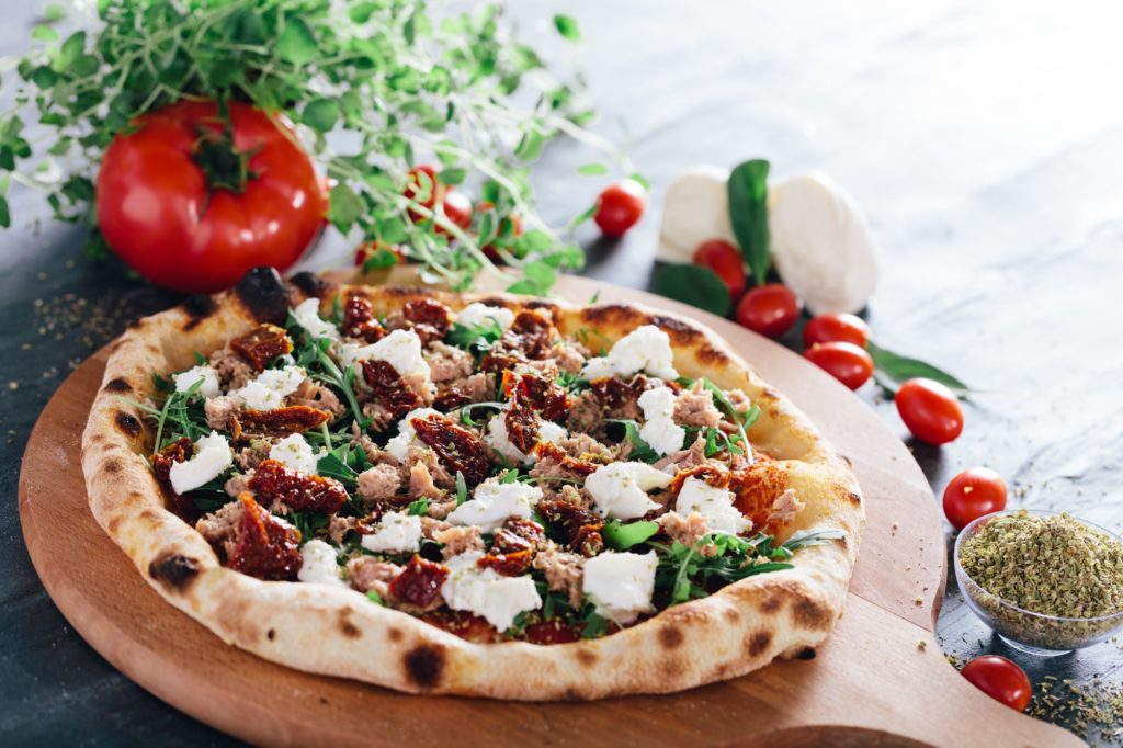 Pizza with dried tomatoes, mozzarella, sausage and rocket